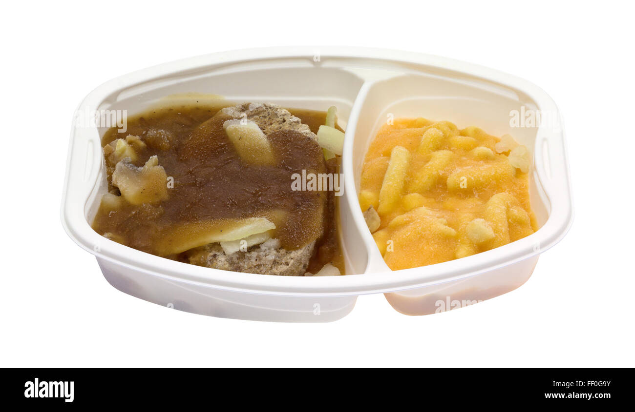 A frozen Salisbury steak plus macaroni and cheese TV dinner in a plastic microwavable tray isolated on a white background. - Stock Image