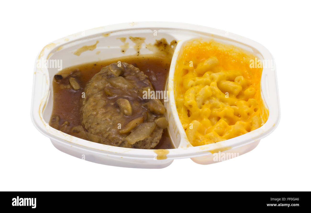 A microwaved Salisbury steak plus macaroni and cheese TV dinner in a plastic tray isolated on a white background. - Stock Image
