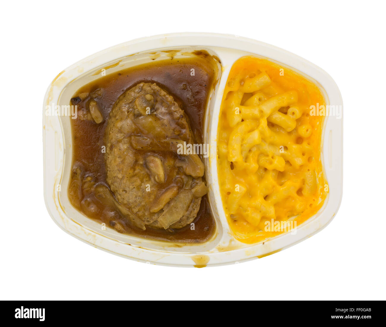 Top view of a microwaved Salisbury steak plus macaroni and cheese TV dinner in a plastic tray isolated on a white - Stock Image