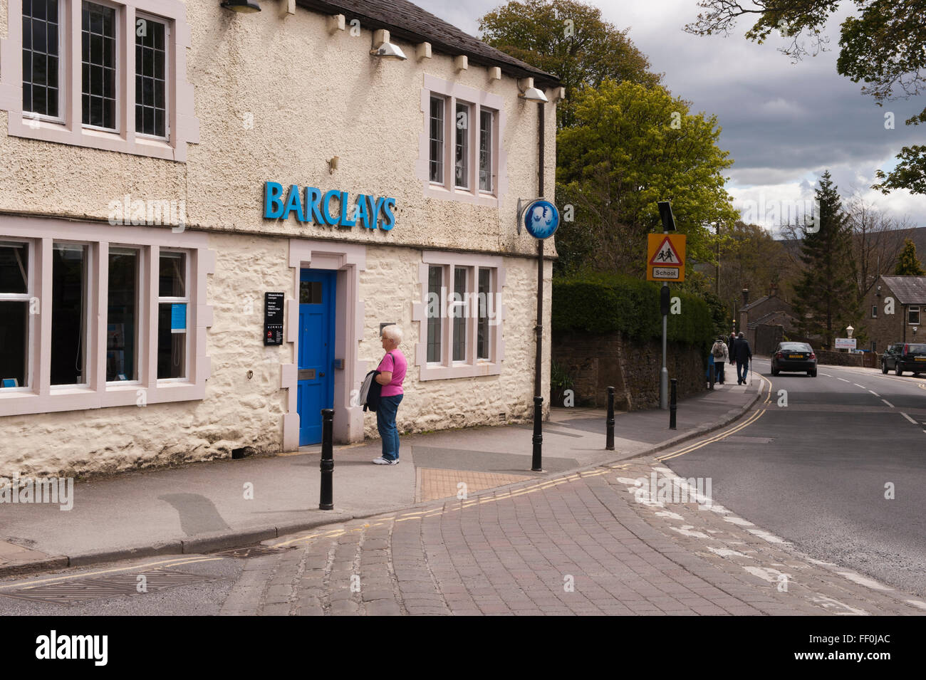 Barclays Bank, Grassington, North Yorkshire, GB, UK, is closed today - a lady studies a sign showing the limited - Stock Image