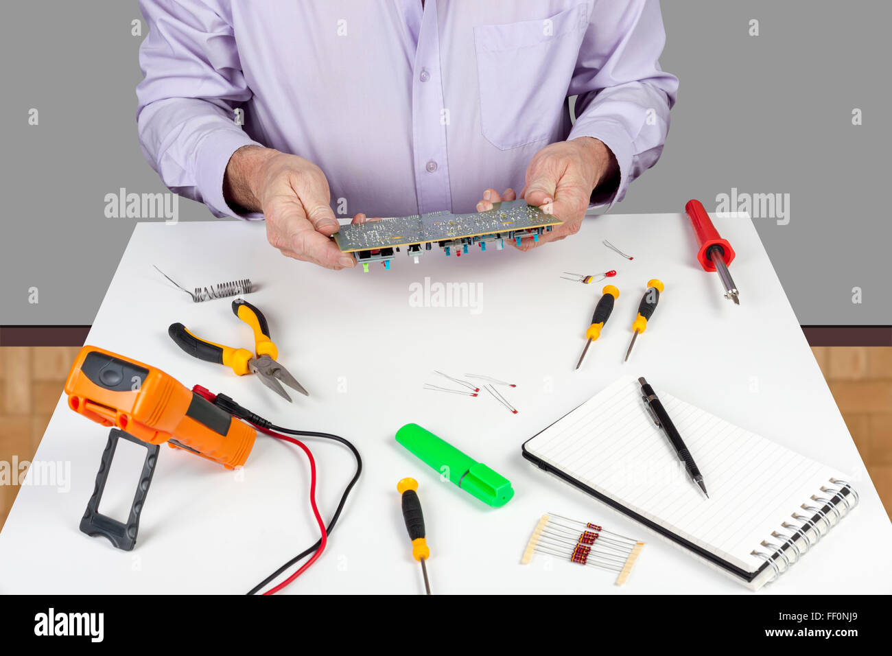 electronic test engineer visually inspecting a faulty printedelectronic test engineer visually inspecting a faulty printed circuit board on his white topped work bench