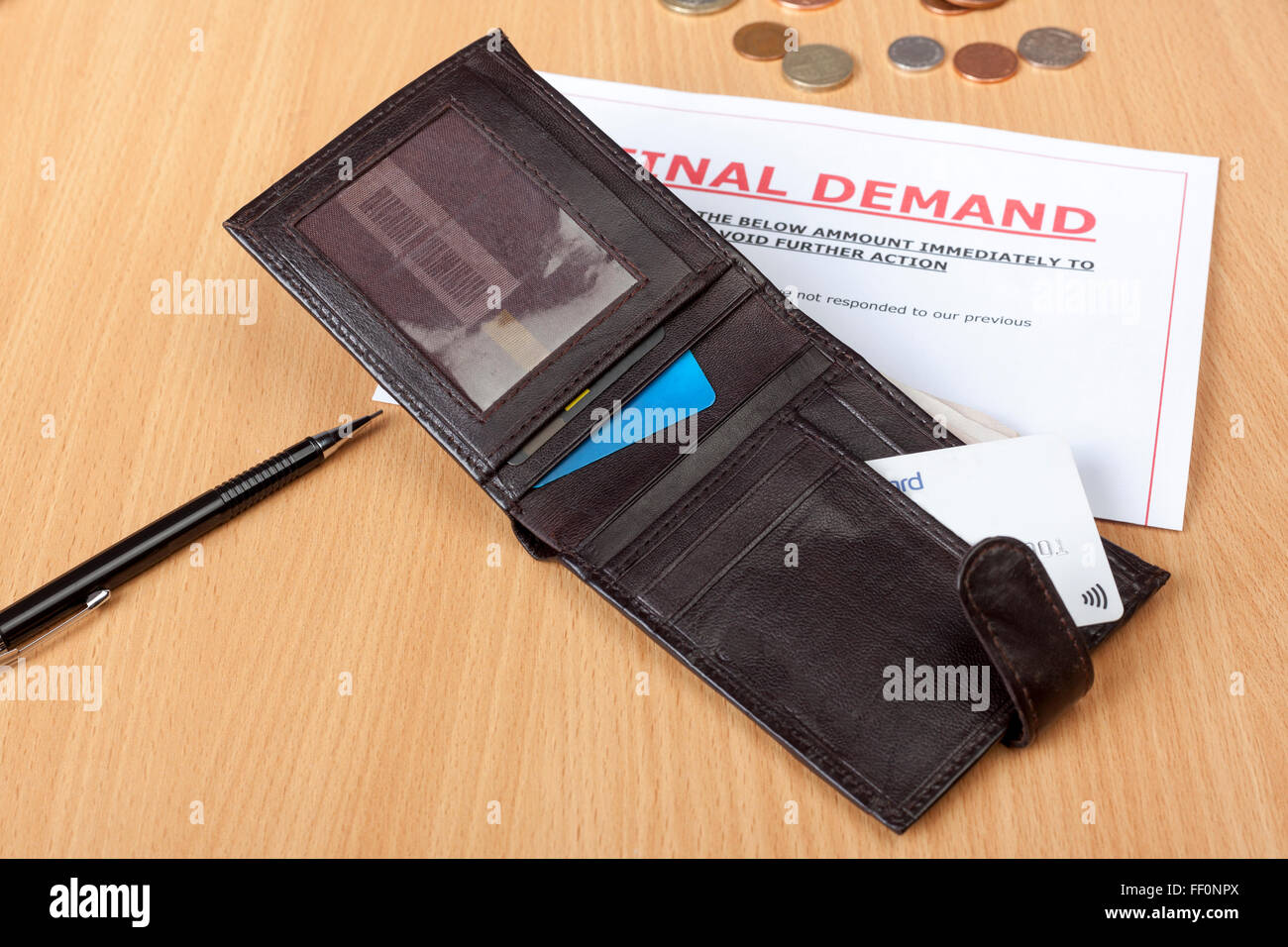 Final demand on a desk with a credit card in a wallet with some cash - Stock Image
