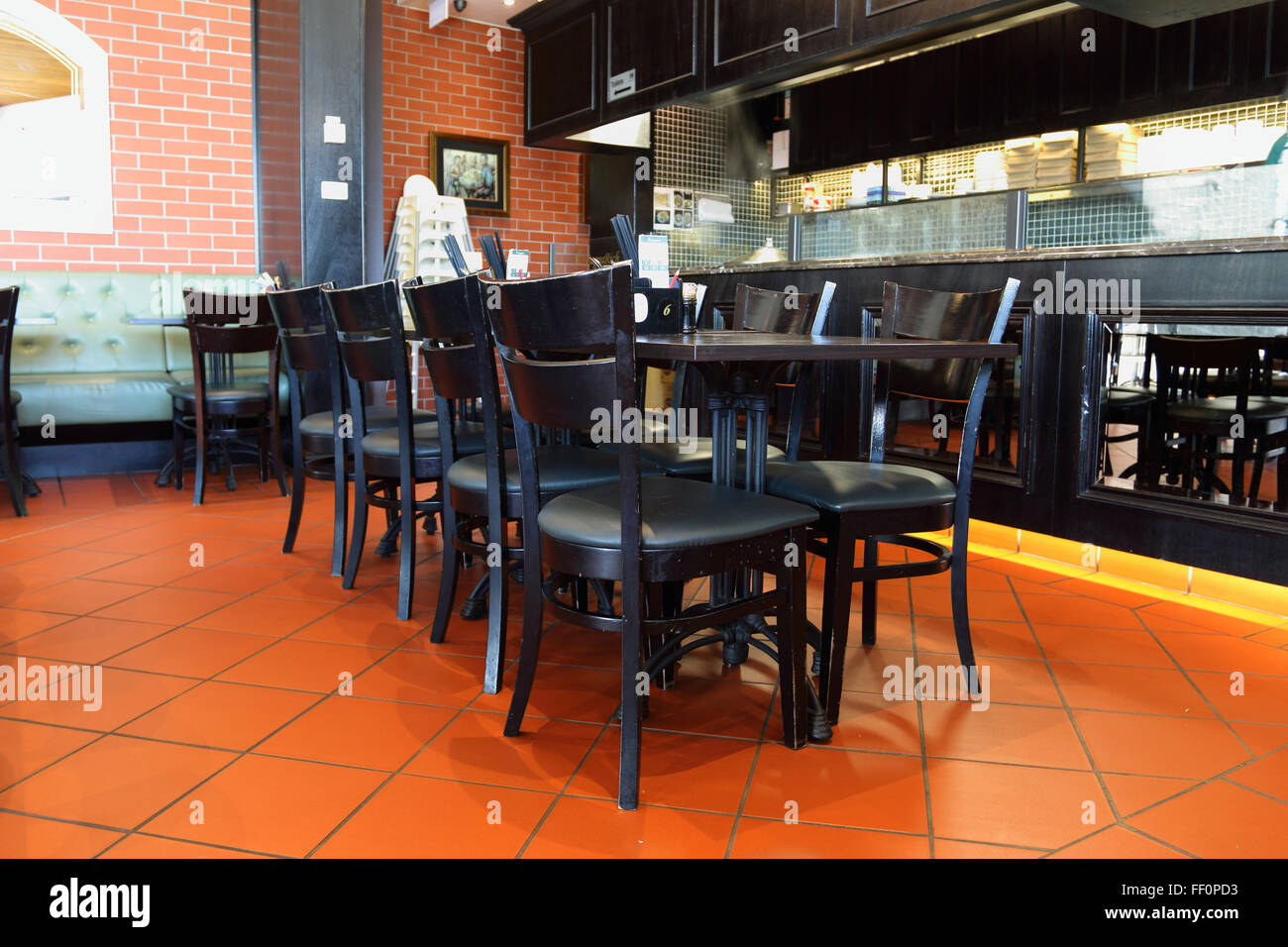 Dining setting in a restaurant with black chairs and tables - Stock Image