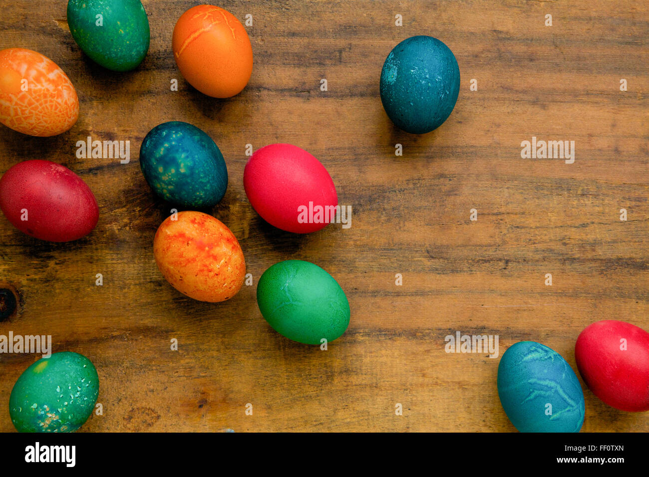 Multicolored dyed easter eggs on a wooden surface. - Stock Image