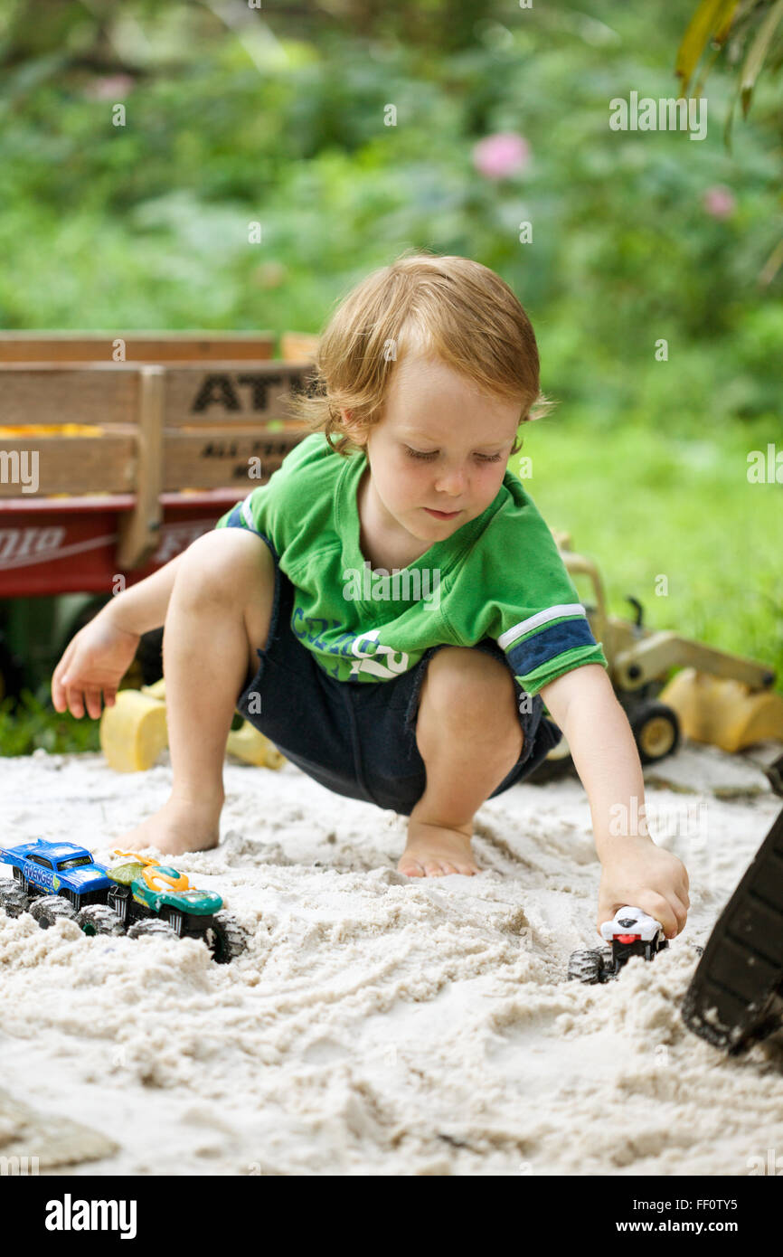 A young boy plays with trucks in a sandbox outdoors. - Stock Image