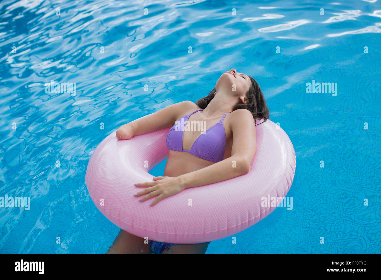 Mixed race amputee woman swimming in pool Stock Photo