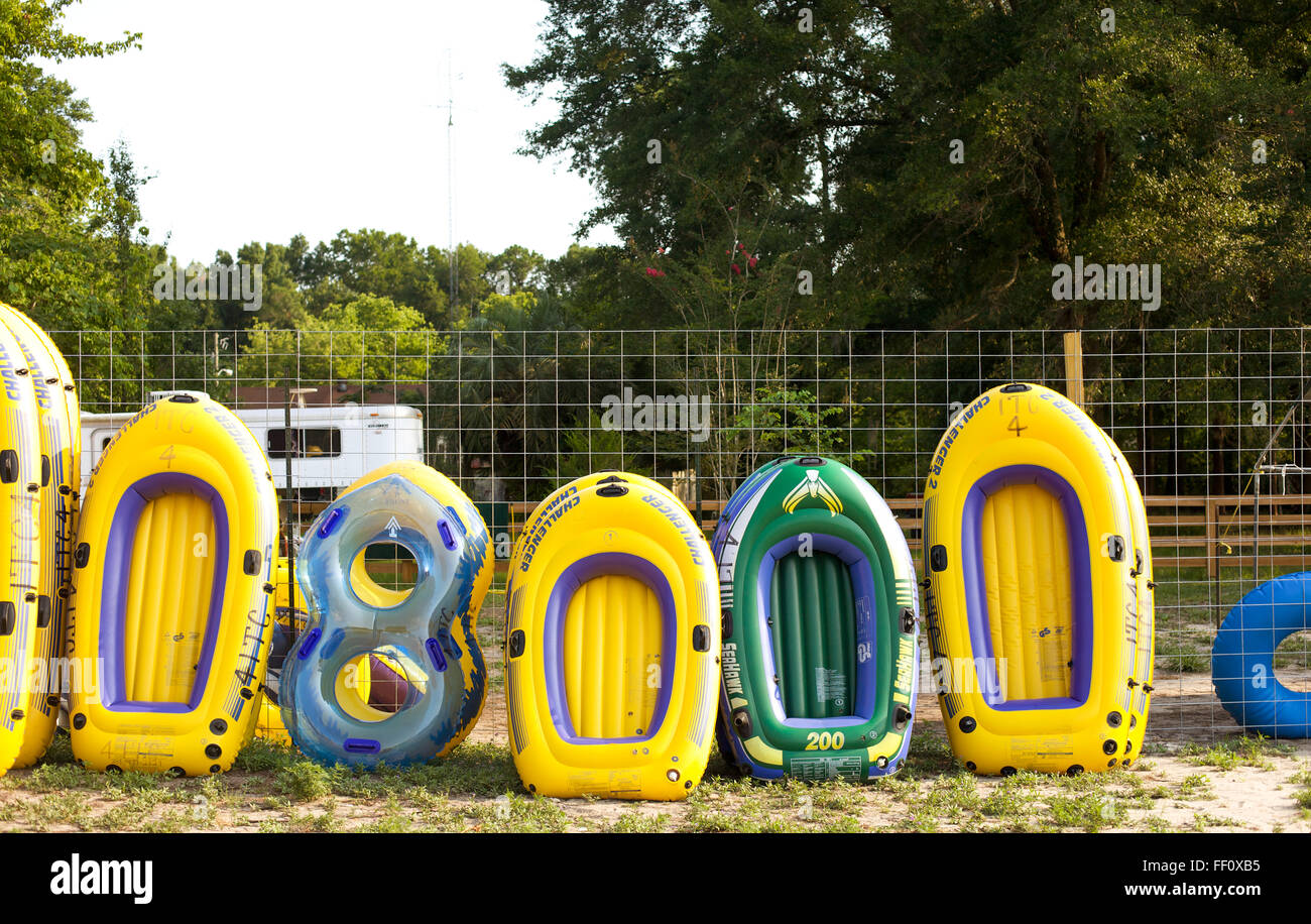 Inflatable rafts leaning up against a fence for people to rent to float down the Ichetucknee river in Fort White - Stock Image