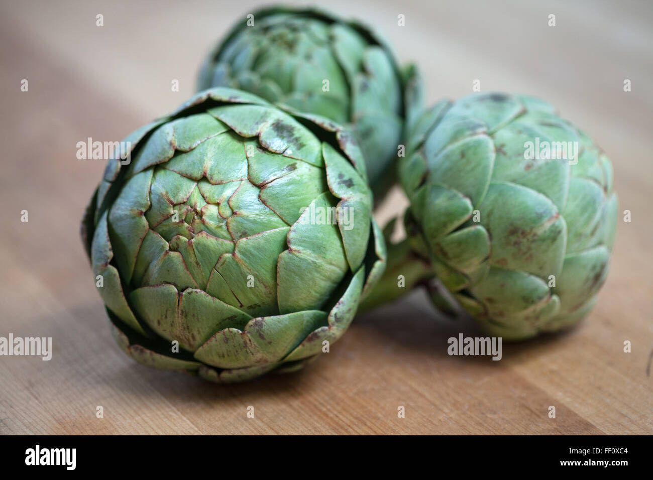Three artichokes sitting on a wooden surface. - Stock Image