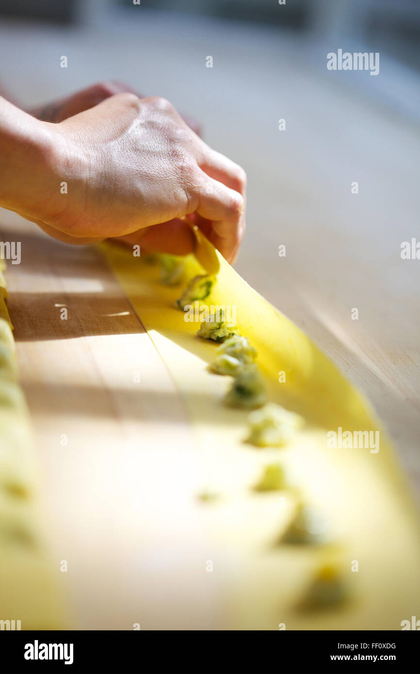 A close-up on hands folding homemade pasta dough over small dots of filling on a wooden counter top. - Stock Image