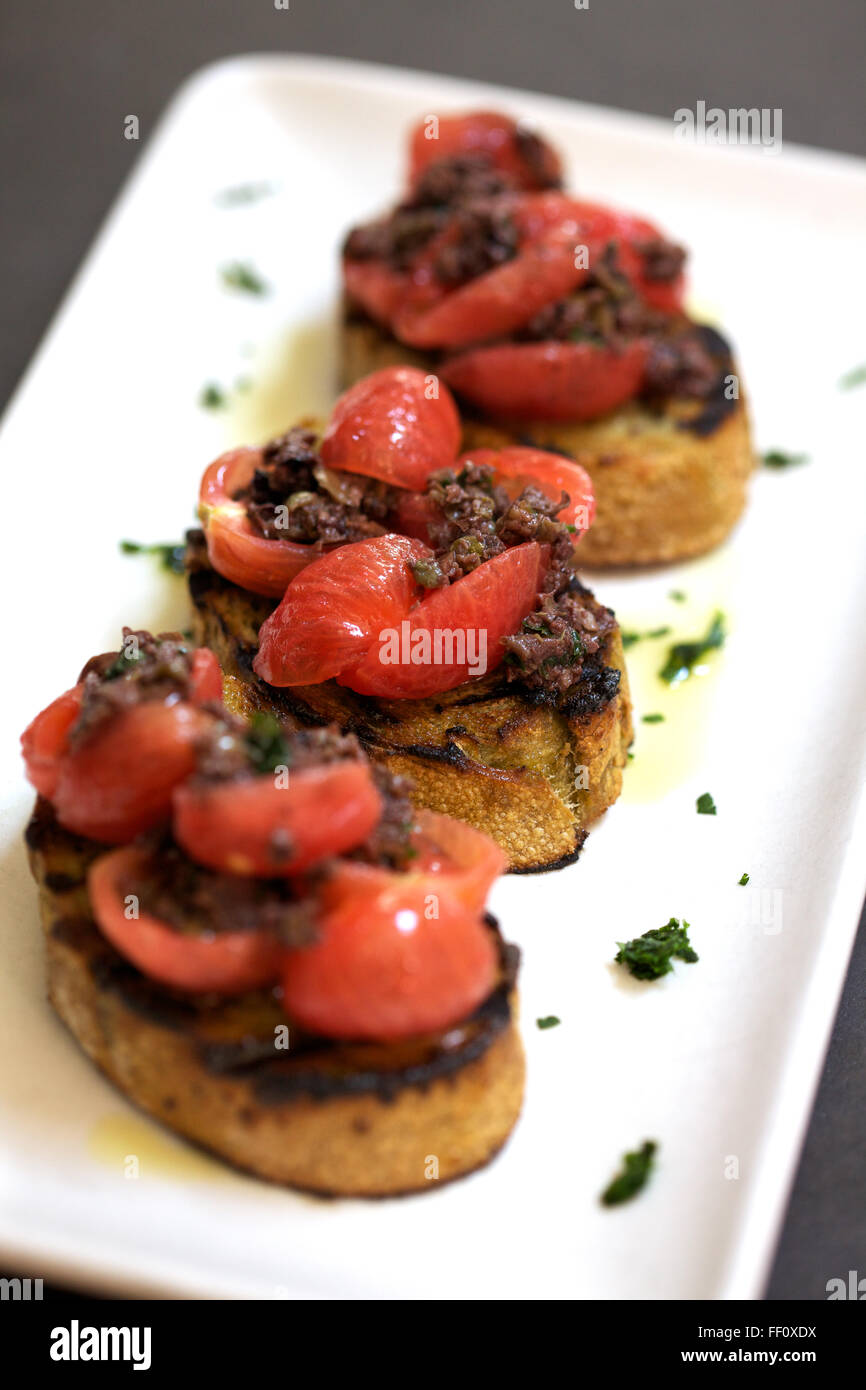 A bite sized appetizer of seasoned meat and cherry tomatoes on top of toast. Stock Photo