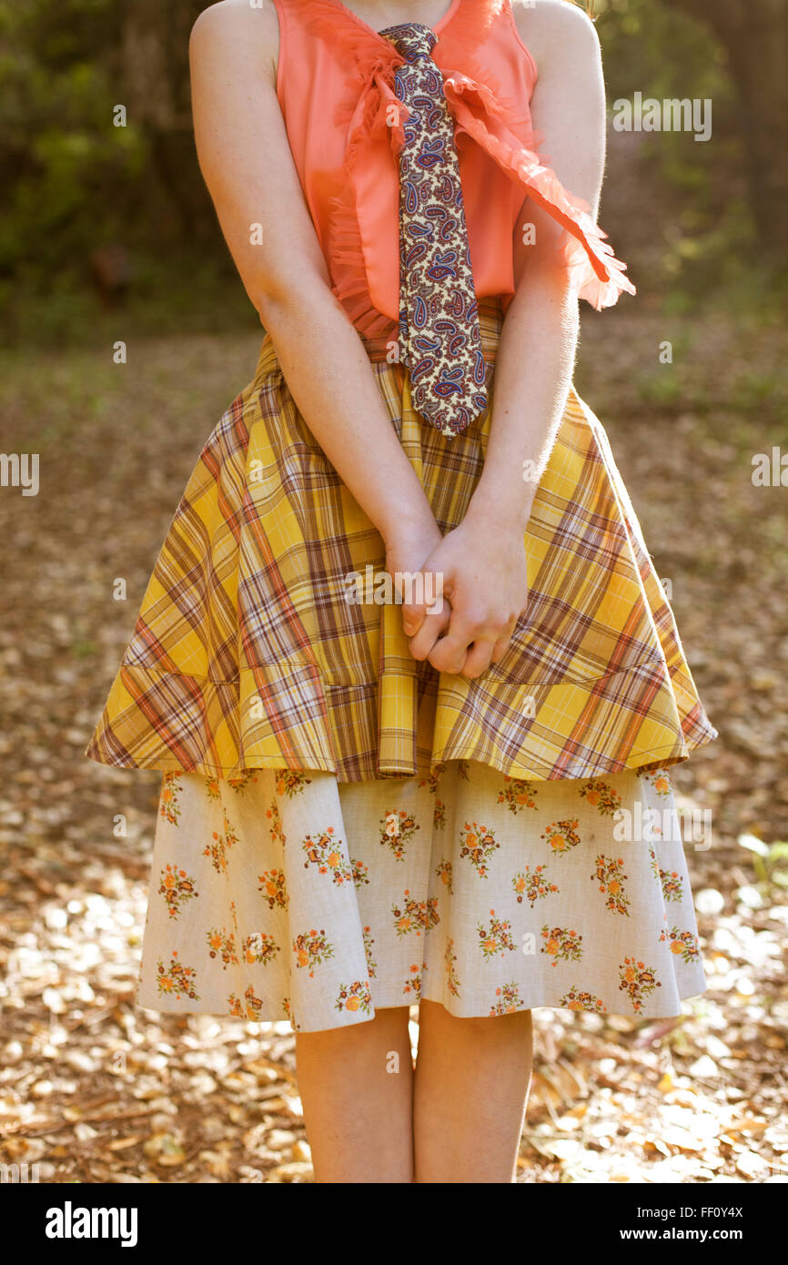 An anonymous young girl with a multi patterned shirt, skirt and tie stands in the sun, shown from the neck down. - Stock Image