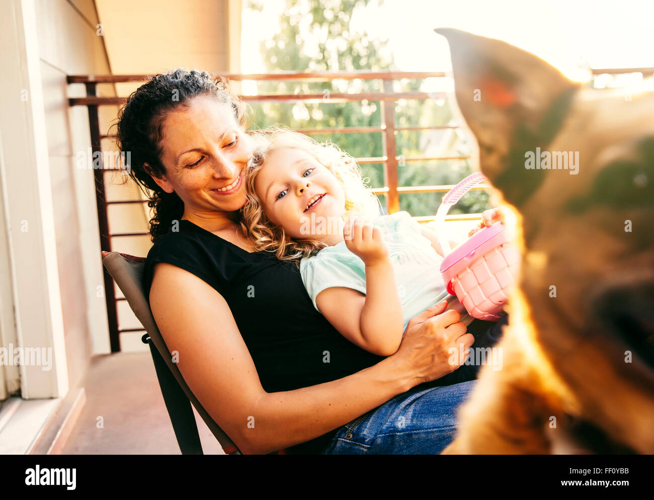 Caucasian mother and daughter playing with dog on patio Stock Photo
