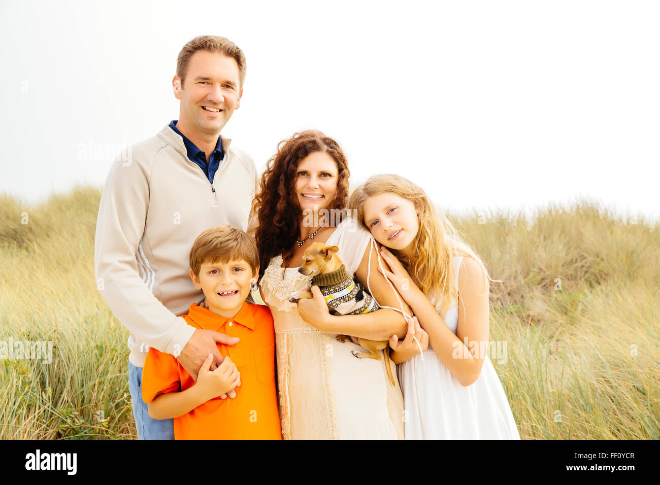 Family smiling with dog on beach Stock Photo