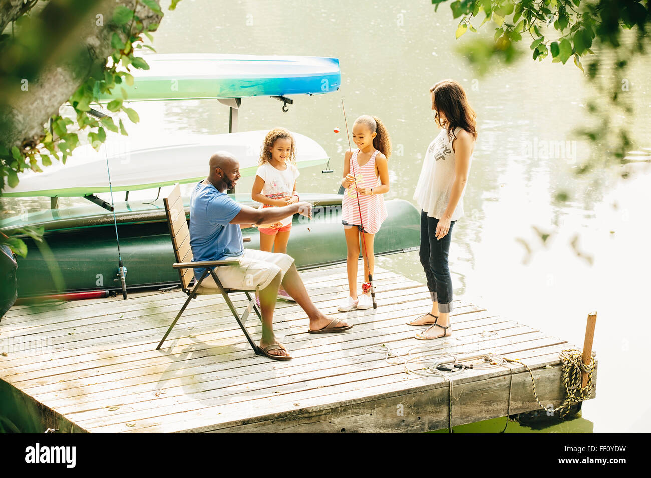 Family standing on dock in lake Stock Photo