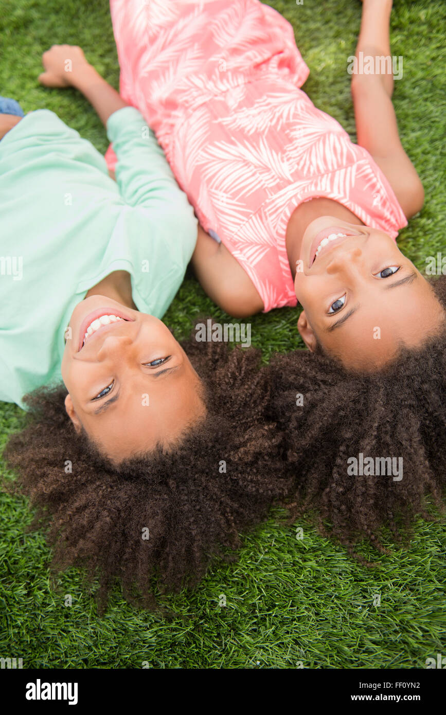 Mixed race sisters laying in grass Stock Photo