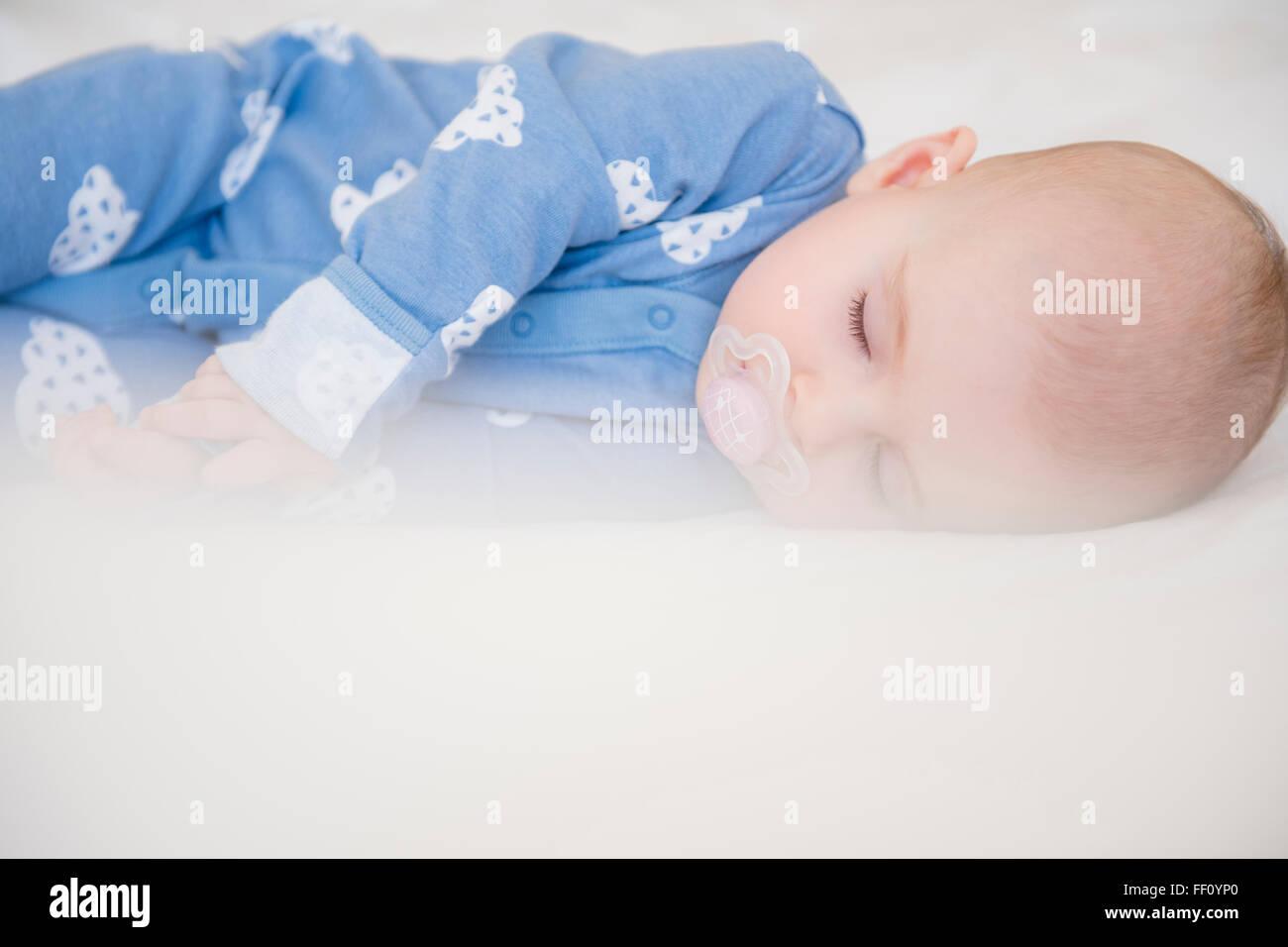Caucasian baby girl sleeping on bed Stock Photo