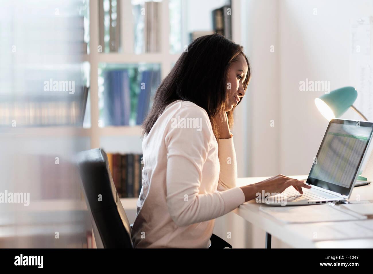 Mixed race businesswoman using laptop Stock Photo