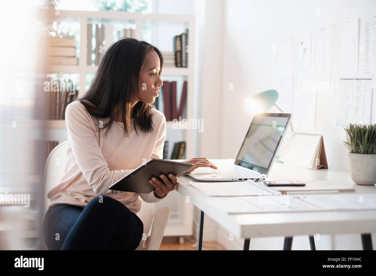 Mixed race businesswoman using laptop Stock Photo
