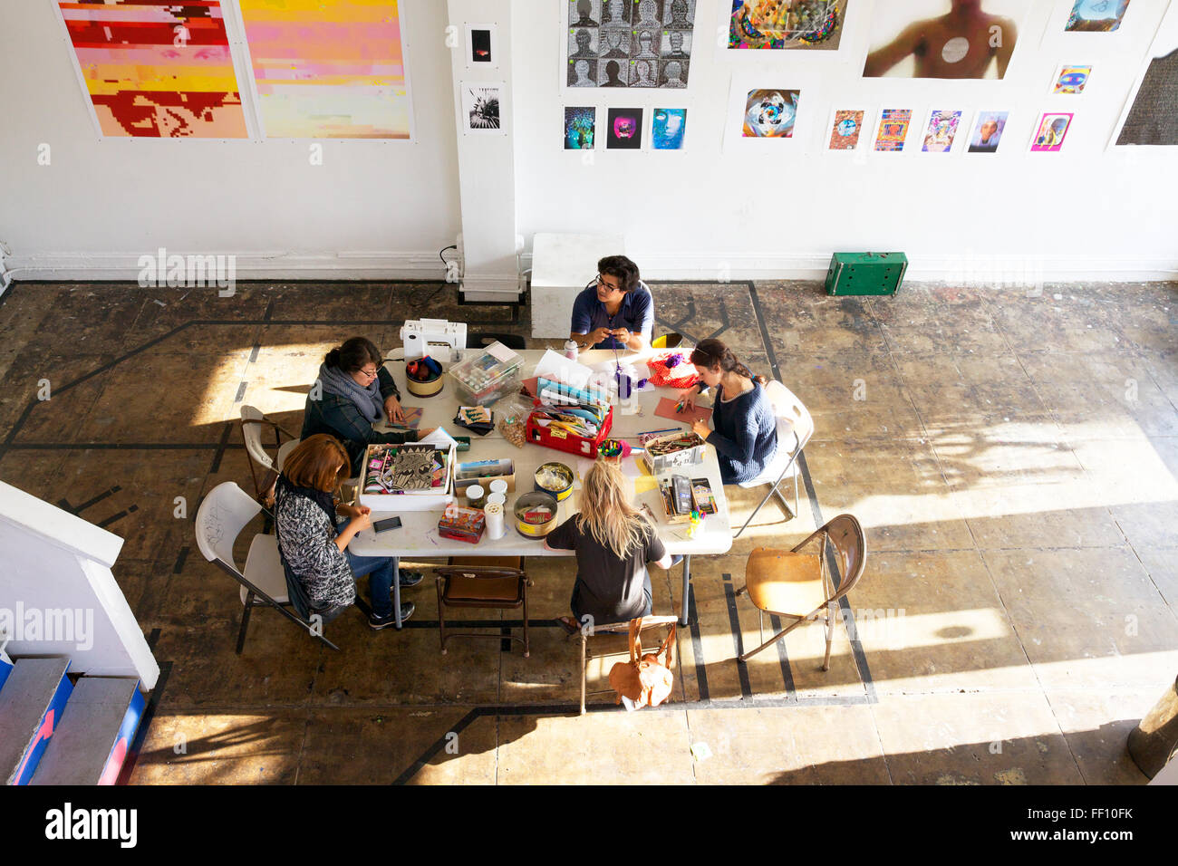 Five people sitting around a table with crafting supplies in a bright sunny space, each working on his or her project - Stock Image