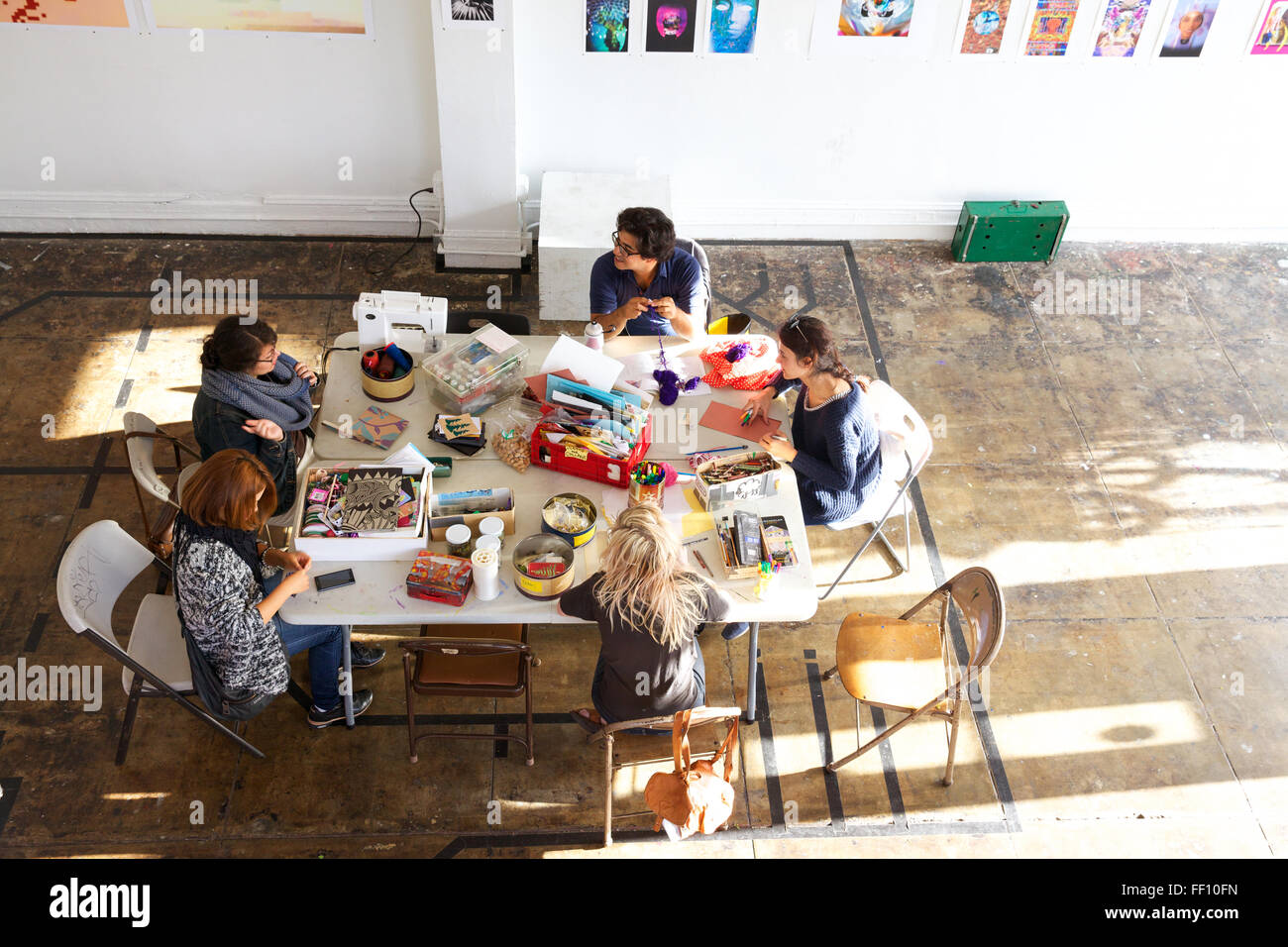 Five people sitting around a table with crafting supplies in a bright sunny space, each working on his or her project Stock Photo