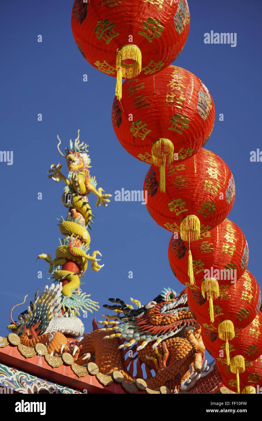 Chinese red lanterns against blue sky and temple roof dragon sculpture - Stock Image
