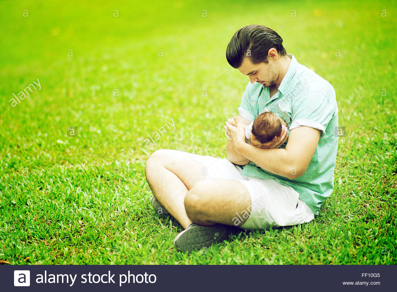 Father Holding New Born Baby at Park - Stock Image