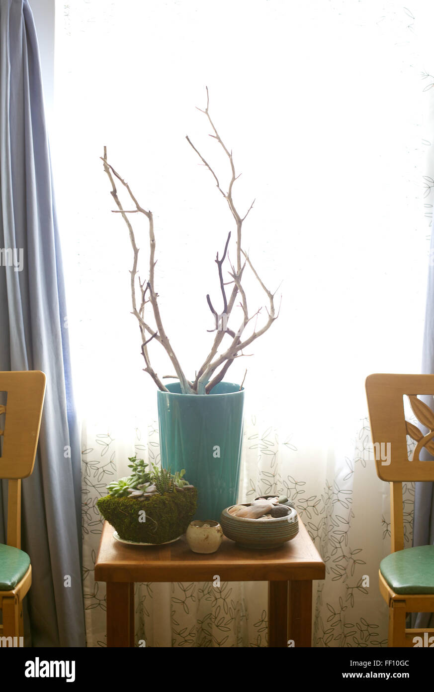 A home interior, two vintage chairs and an arrangement of vases and plants on display in front of a window. - Stock Image