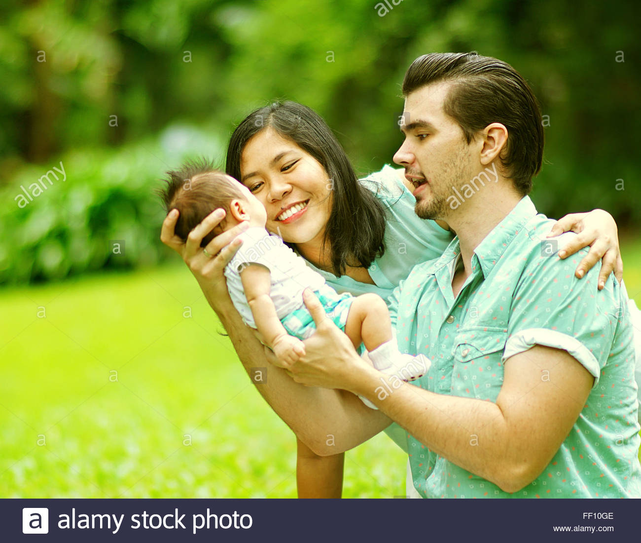 Happy Mixed Race Family Playing with New Born Baby at Park - Stock Image