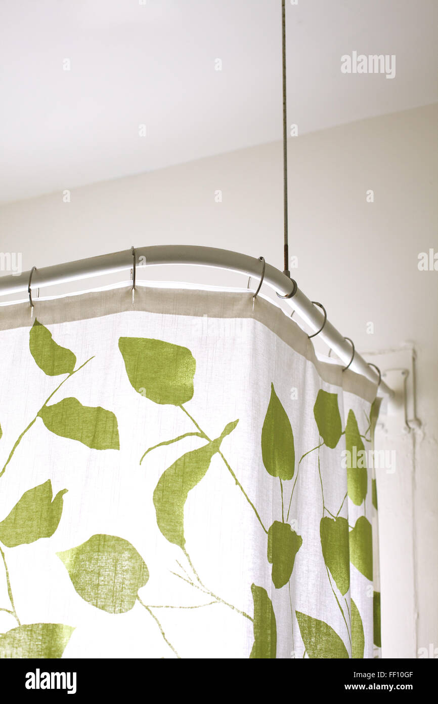 The top of a shower curtain, white with a green leaf pattern. - Stock Image
