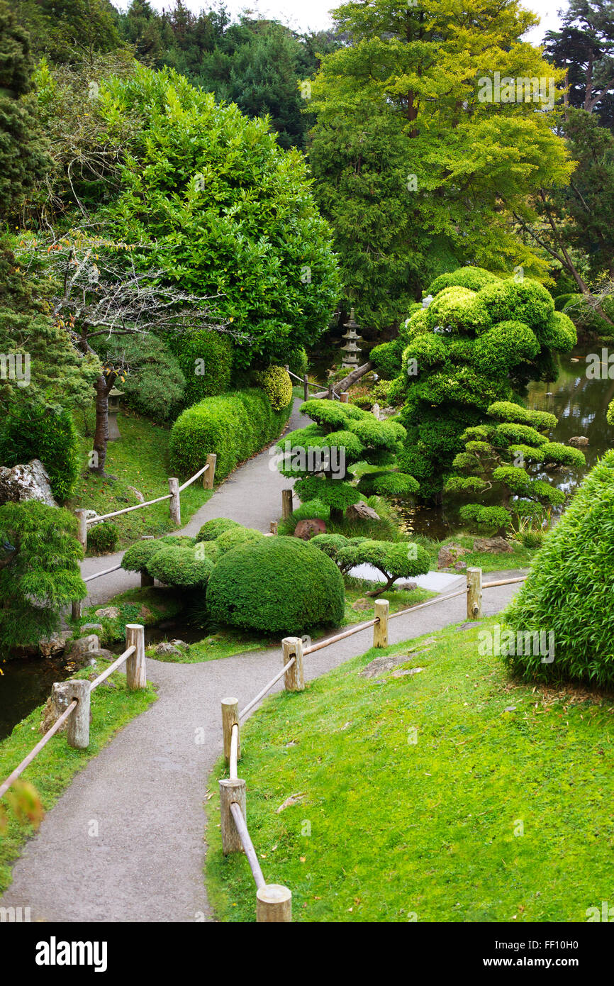 A pathway winding though a Japanese garden, the bushes, trees and grass are all vibrant green. - Stock Image