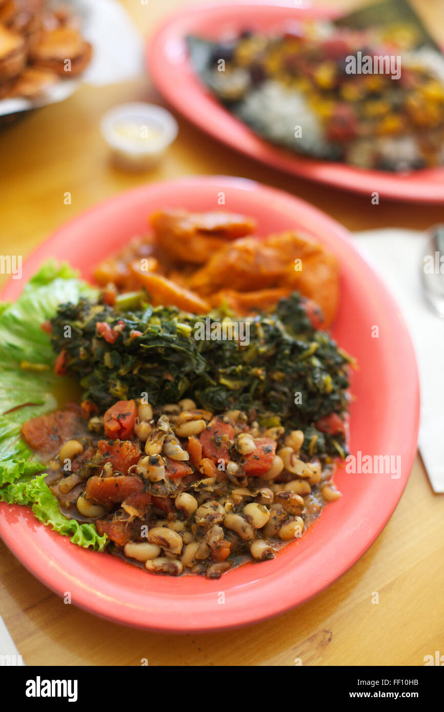 A healthy meal of vegan soul food including black eyed peas and a healthy meal of vegan soul food including black eyed peas and greens served on a bright salmon pink plate 45 degree angle forumfinder Choice Image