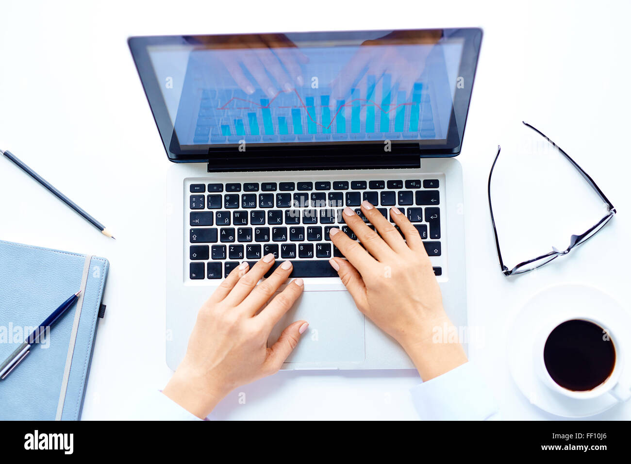 Human hands typing on laptop in business environment - Stock Image