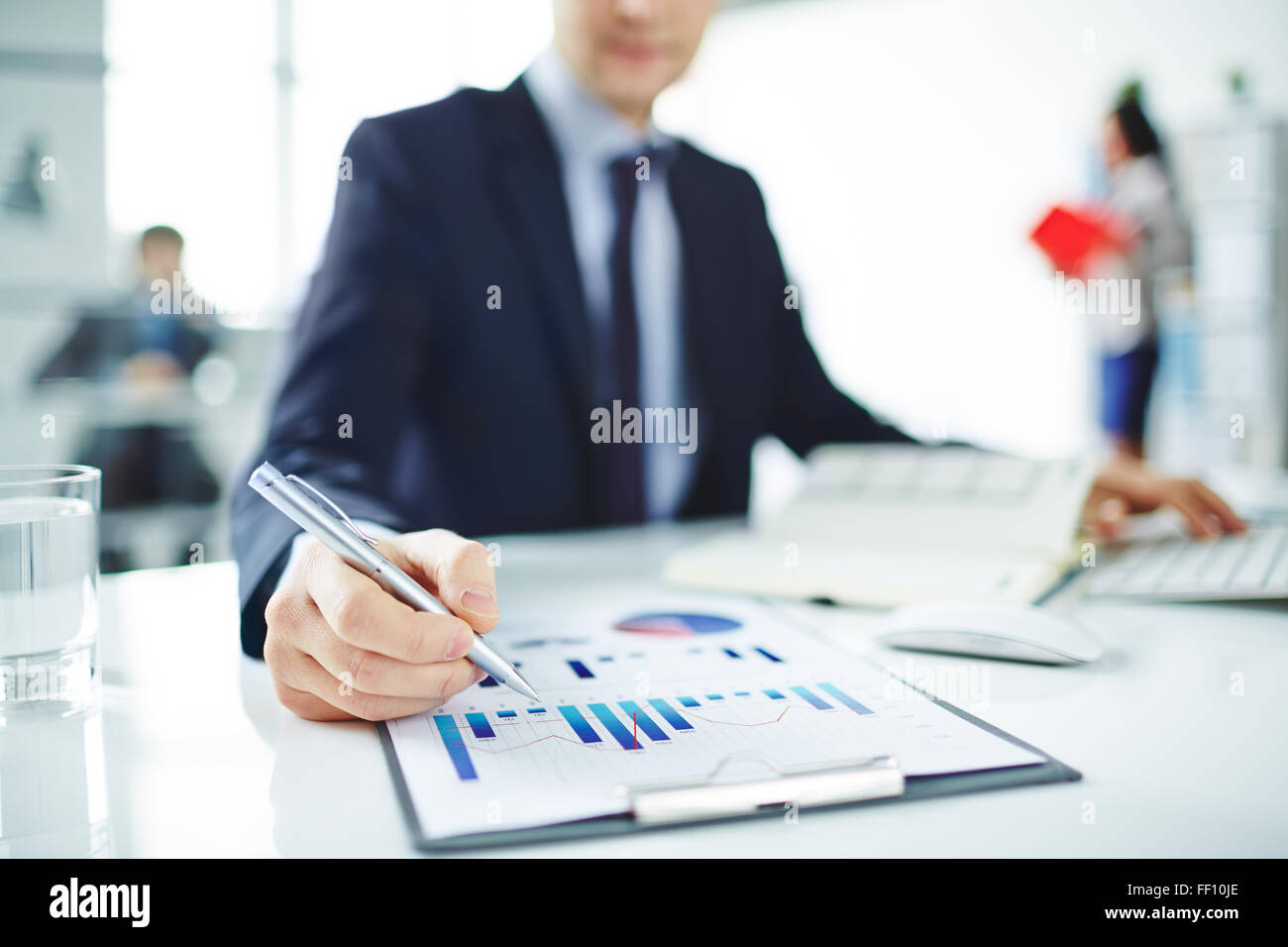 Young businessman pointing at chart in document in office - Stock Image