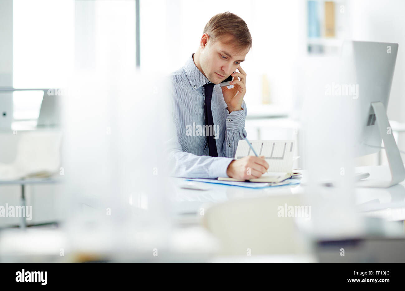 Young businessman speaking on the phone and making notes in notepad in office - Stock Image