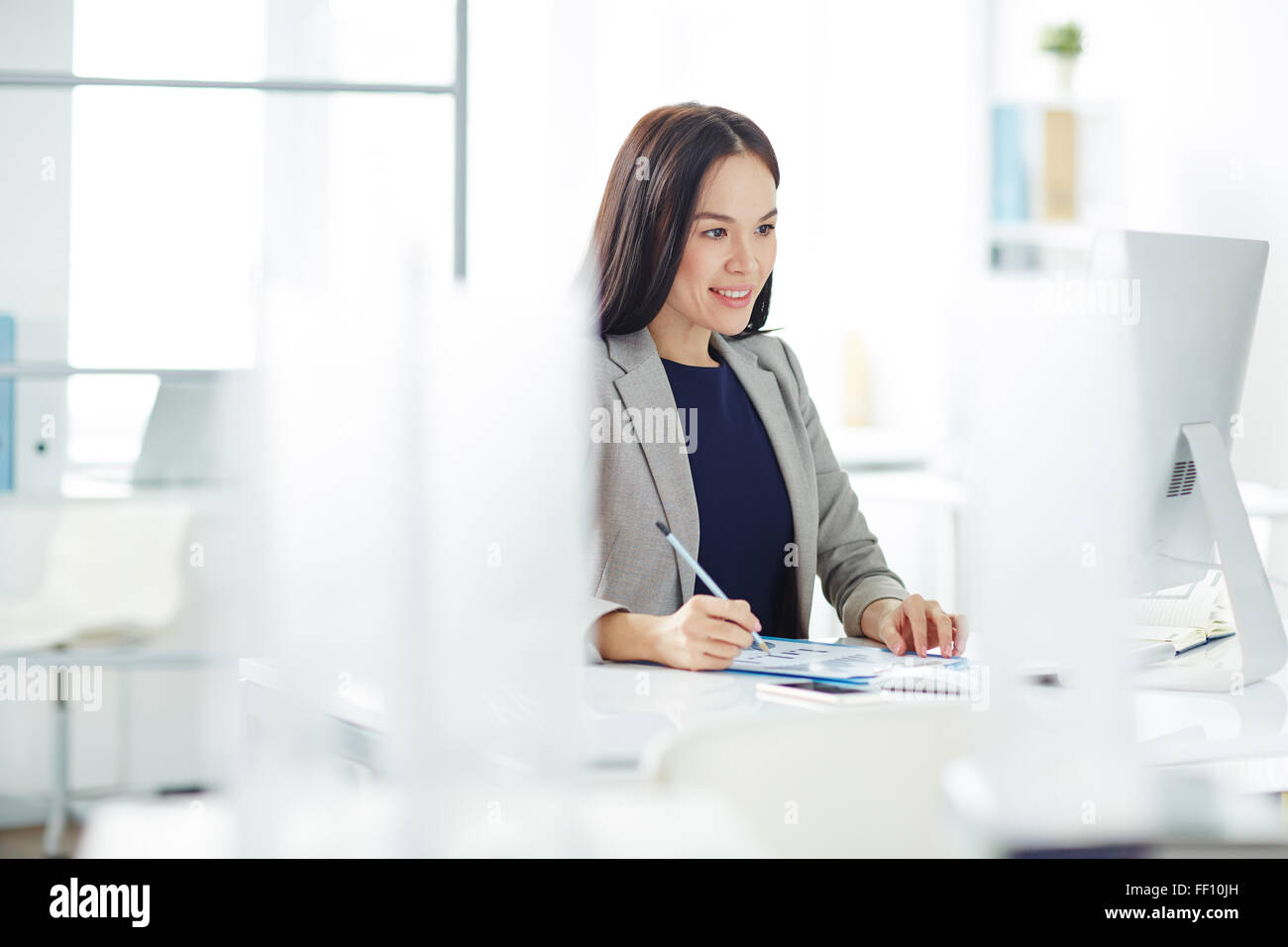 Pretty secretary analyzing data and looking at monitor in office - Stock Image