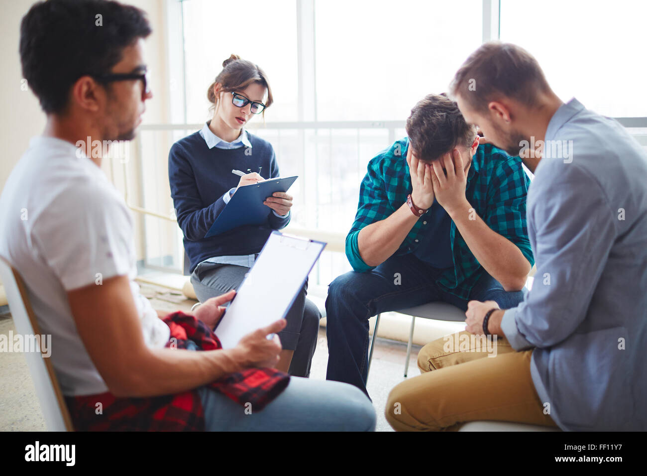 Group of helpful students supporting their despaired friend - Stock Image