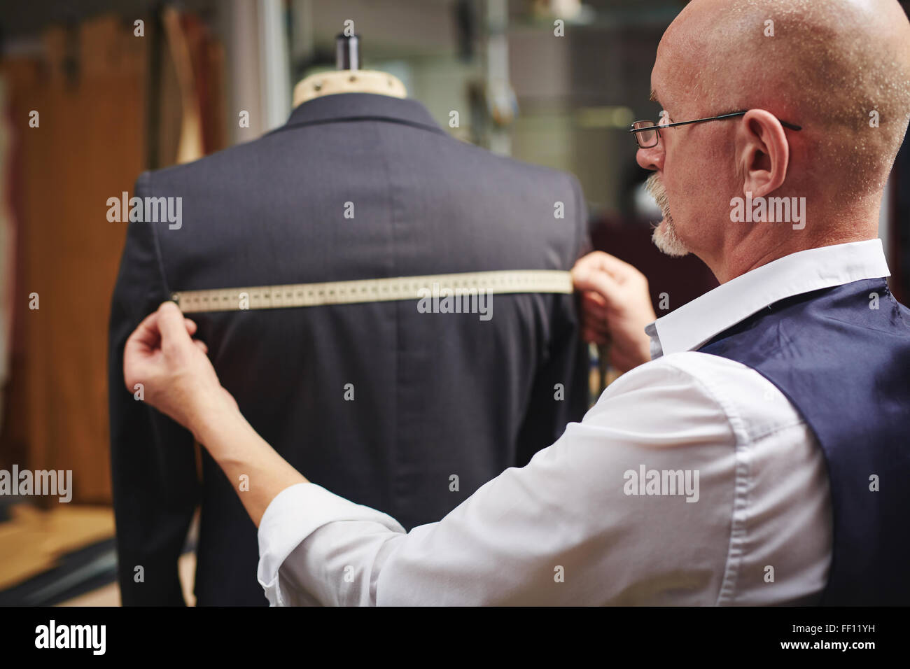 Mature tailor measuring back of jacket at work - Stock Image