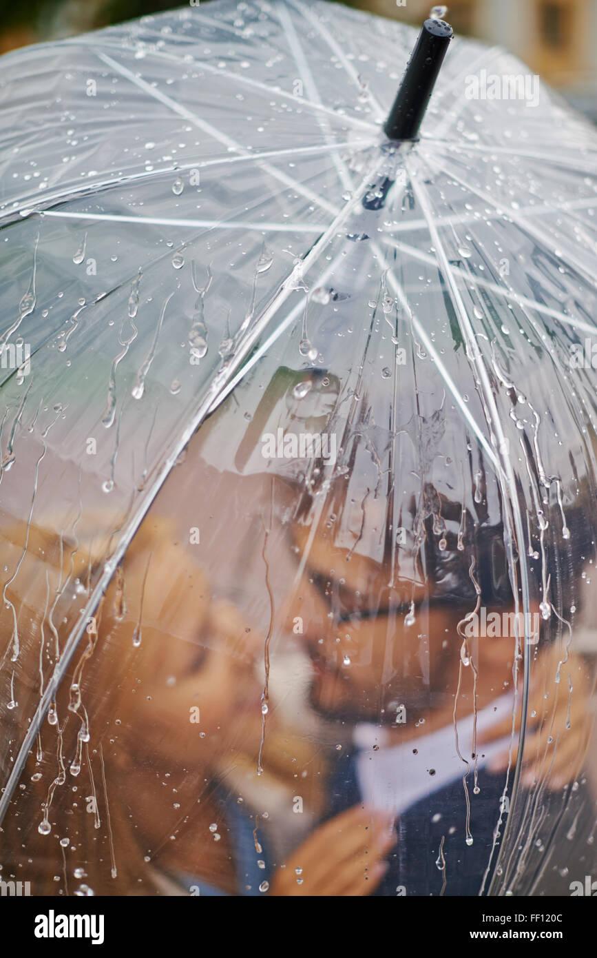 Romantic valentines standing under umbrella in the rain - Stock Image