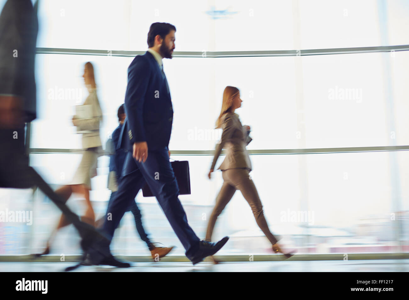 Crowd of modern business people walking down corridor - Stock Image