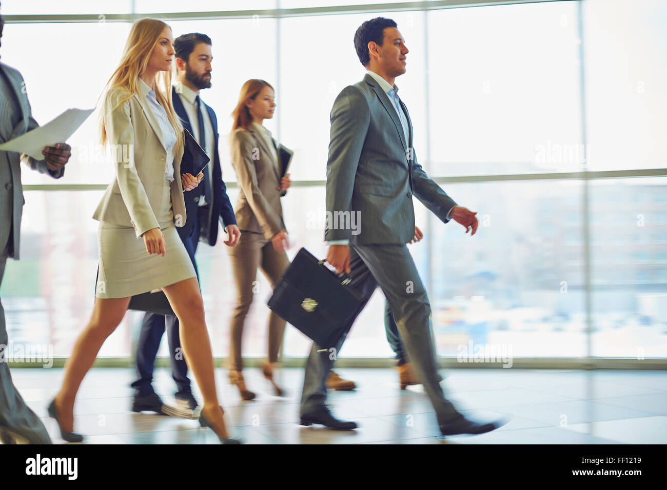 Crowd of business people going down corridor of office building in the morning - Stock Image