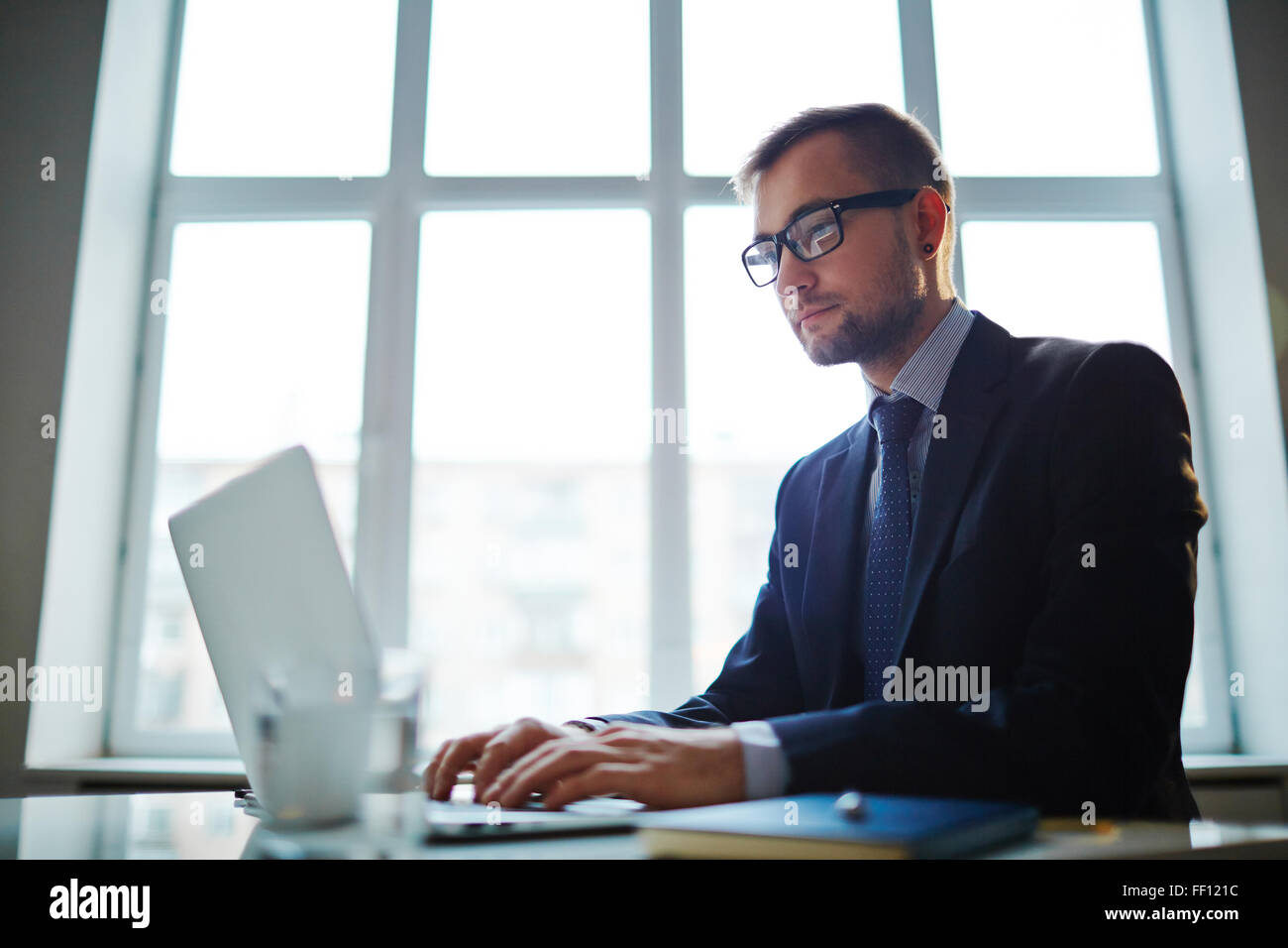 Confident young businessman analyzing electronic data in office - Stock Image