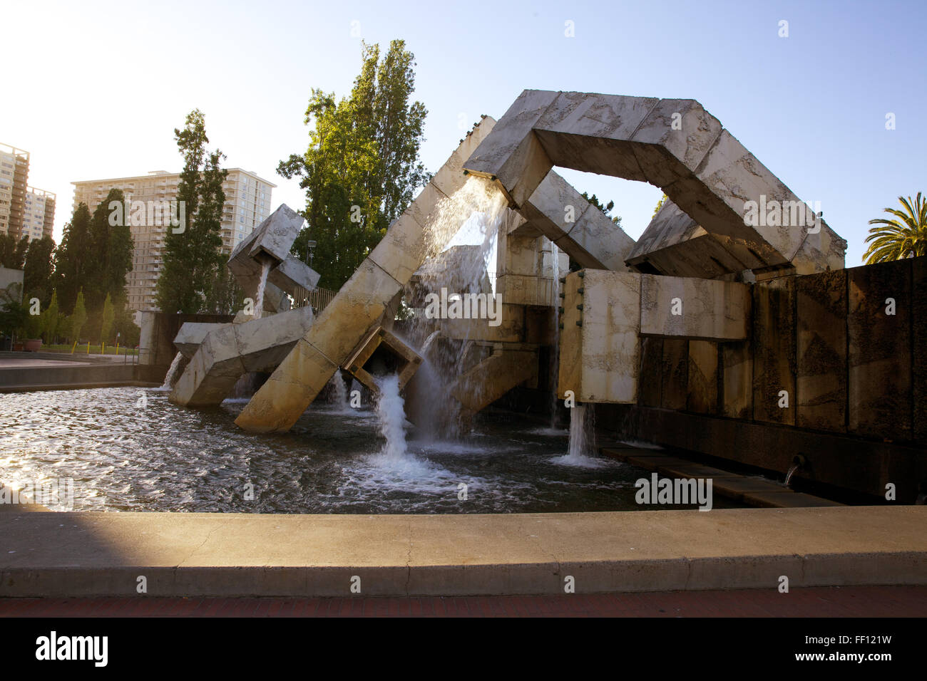 The Vaillancourt Water Fountain in Justin Herman Plaza with water flowing and the sun shining behind it. - Stock Image