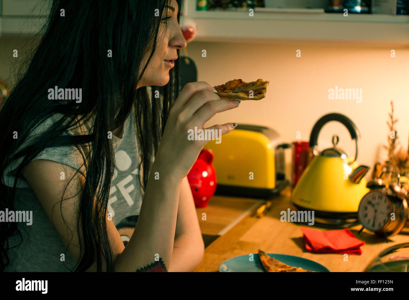 Caucasian woman eating pizza in kitchen Stock Photo