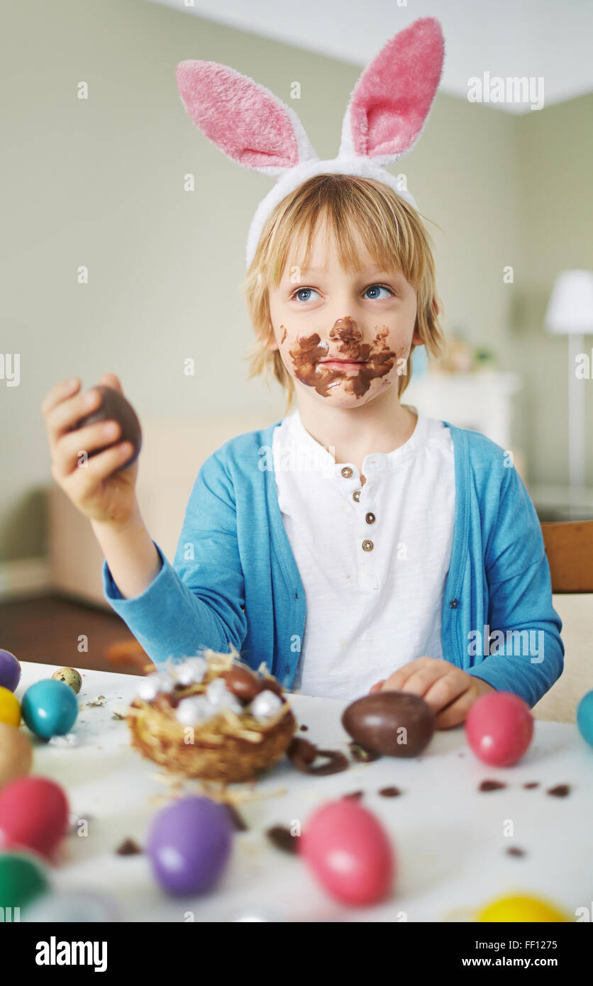 Cute boy with rabbit ears eating chocolate Easter eggs - Stock Image