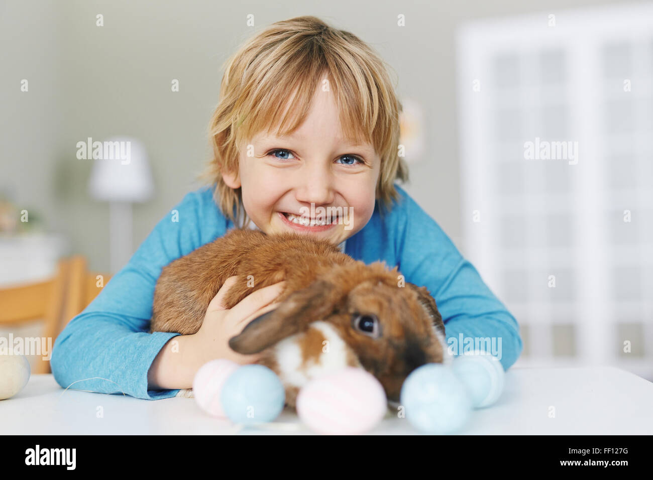 Joyful youngster with Easter rabbit looking at camera - Stock Image