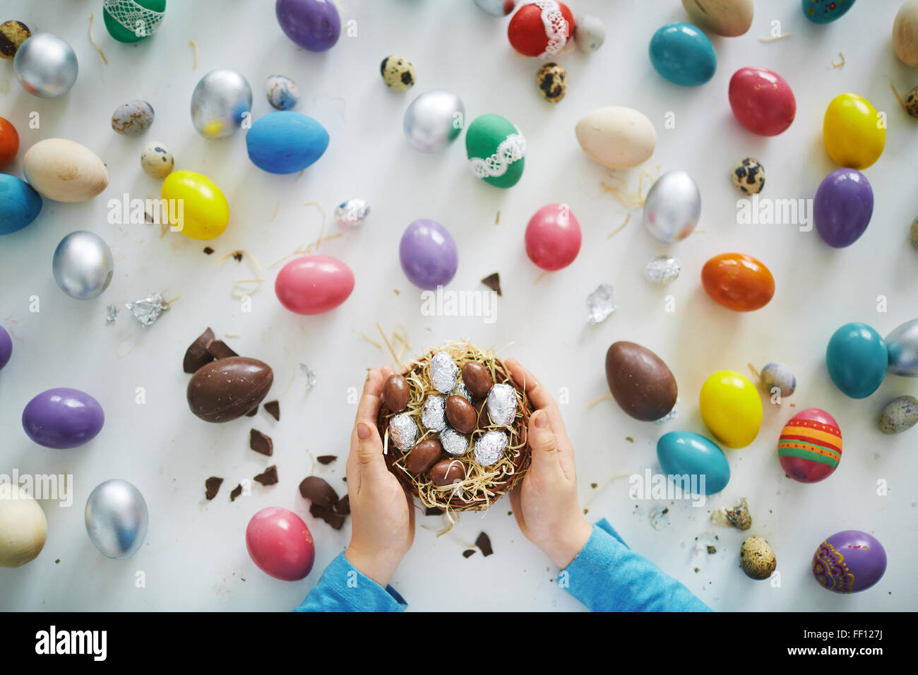Hands of child holding small nest or basket with chocolate Easter eggs over painted ones - Stock Image