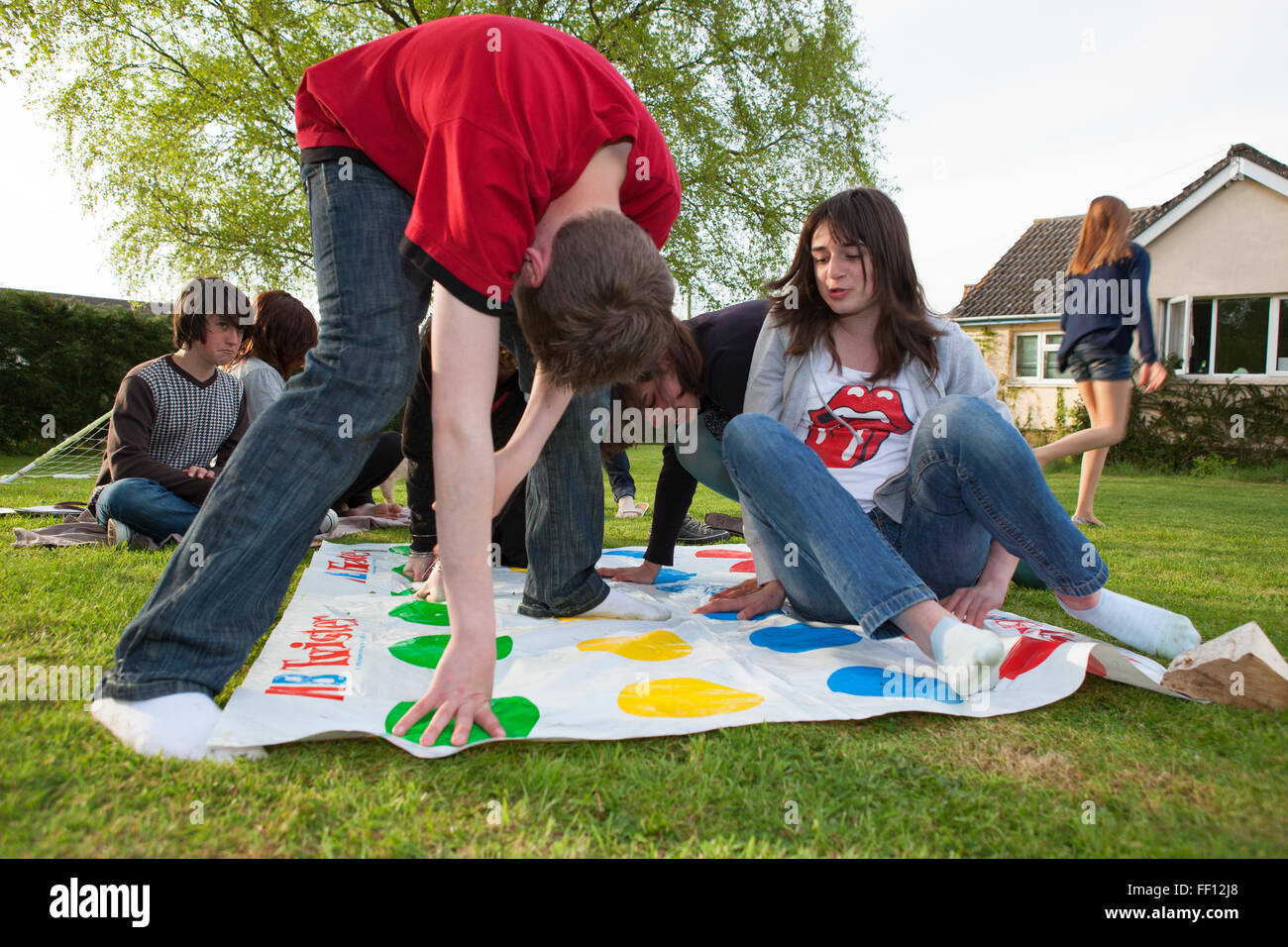 Group of happy children playing the Twister game on the lawn - Stock Image