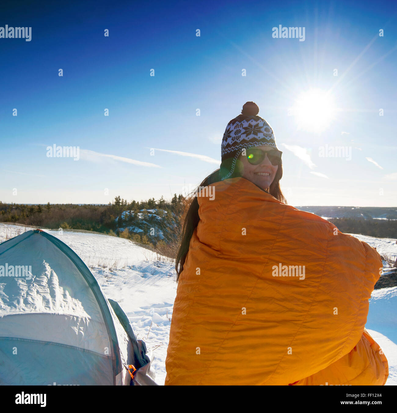 Hiker standing at snowy campsite - Stock Image