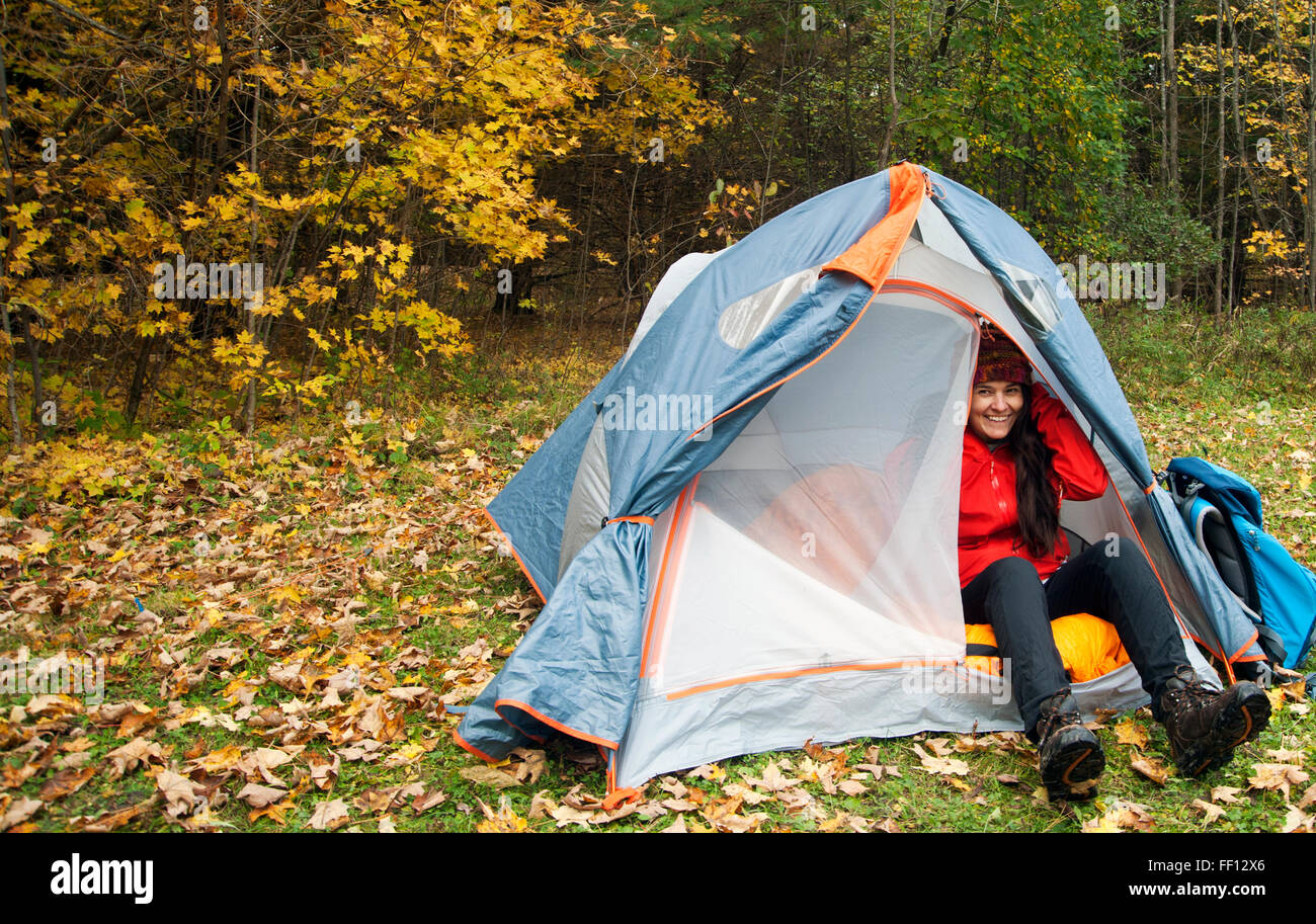Hiker sitting in tent at campsite - Stock Image