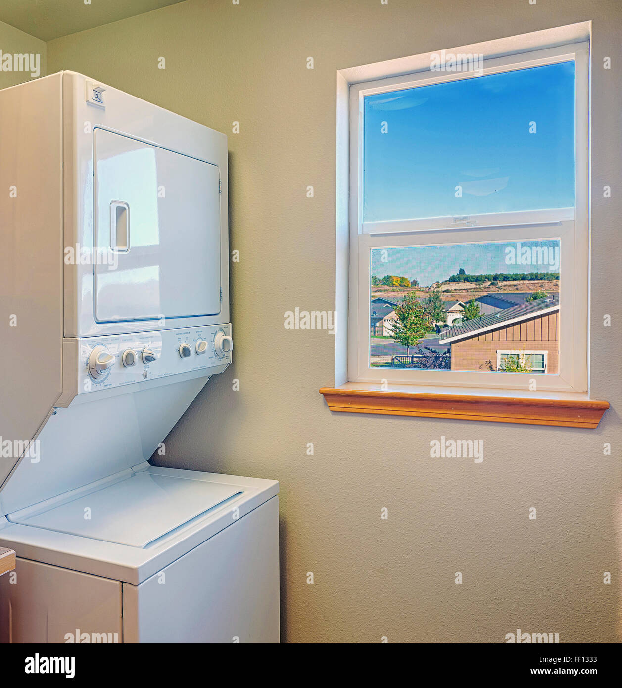 Washer and dryer with window in laundry room - Stock Image